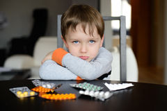 Sad preschooler sitting at the table with pills Stock Images