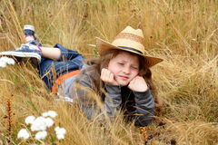 Sad preteen country girl. A sad young frowning preteen little girl with long blond hair wearing a hat laying in a field of tall grass and white wild Queen Anns Stock Photography
