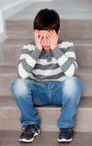 Sad preteen sitting on the stairs at home Royalty Free Stock Image