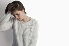 Sad pretty brunette leaning against wall Royalty Free Stock Images