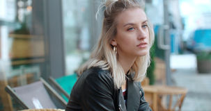 Sad pretty caucasian girl sitting at outdoors cafe and waiting for somebody. Stock Images