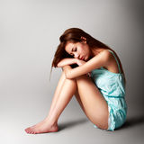 Sad pretty girl sitting on the floor Royalty Free Stock Image