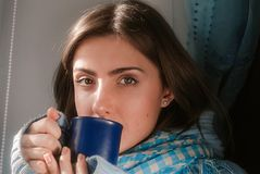 Sad pretty girl staying home because of the flu and temperature in warm sweater and scarf Royalty Free Stock Image