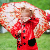 Sad pretty little girl in red raincoat with umbrella walking in park summer Stock Photo