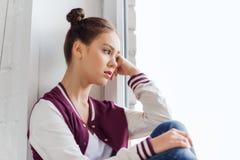 Sad pretty teenage girl sitting on windowsill Royalty Free Stock Photo