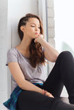 Sad pretty teenage girl sitting on windowsill Royalty Free Stock Image