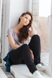 Sad pretty teenage girl sitting on windowsill Royalty Free Stock Images