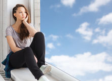 Sad pretty teenage girl sitting on windowsill Stock Photos