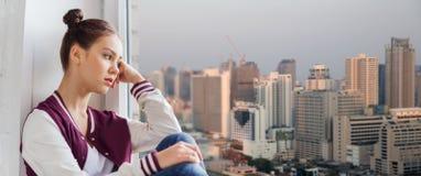 Sad pretty teenage girl sitting on windowsill Stock Images