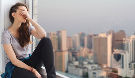Sad pretty teenage girl sitting on windowsill Stock Photo