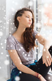 Sad pretty teenage girl sitting on windowsill Royalty Free Stock Photography