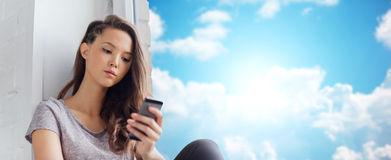 Sad pretty teenage girl with smartphone texting. People, technology and teens concept - sad unhappy pretty teenage girl sitting on windowsill with smartphone and Royalty Free Stock Photography