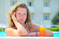 Sad pretty woman is boring in the hotel pool Royalty Free Stock Images