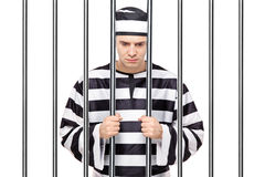 A sad prisoner in jail holding bars. A view of a sad prisoner in jail holding bars isolated on white background Stock Photos