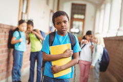 Sad pupil being bullied by classmates at corridor Royalty Free Stock Photos