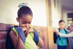 Sad pupil being bullied by classmates at corridor Royalty Free Stock Image