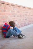 Sad pupil sitting alone in corridor Stock Photo