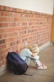 Sad pupil sitting alone on ground Royalty Free Stock Image