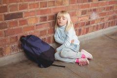 Sad pupil sitting alone on ground Stock Image