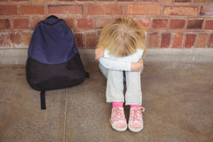 Sad pupil sitting alone on ground Stock Photo