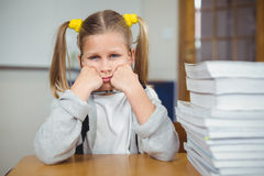 Sad pupil sitting at her desk in a classroom Stock Images