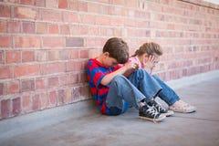 Sad pupils sitting in corridor Stock Photo