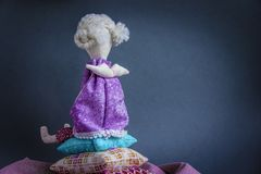 A sad puppet angel. A sad puppet angel with wings in a purple dress sits on colored pillows turning away from the wall Stock Image