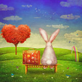 Sad rabbit  with suitcase sitting on the bench on the glade Royalty Free Stock Photo