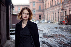 Sad red-haired girl on the background of industrial landscape. Woman walking Stock Photo