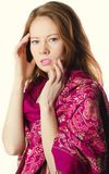 Sad red-haired girl in crimson toga. Holding his head royalty free stock images