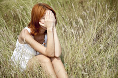 Sad red-haired girl at grass. Royalty Free Stock Photo