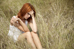 Sad red-haired girl at grass. Royalty Free Stock Images