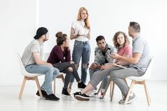Sad red-haired girl talking about depression during group meeting with therapist stock image