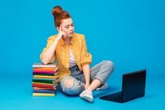 Sad red haired teenage student girl with laptop stock photos