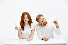 Sad redhead girl and boy holding cups of coffee. And sitting at white desk over white background Stock Image
