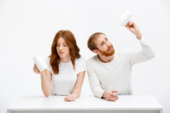 Sad redhead girl and boy holding cups of coffee  sitting. Sad redhead girl and boy holding cups of coffee and sitting at white desk over white background Stock Images