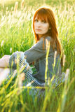 Sad redhead woman in grass Stock Images