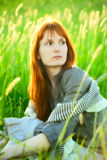 Sad redhead woman in grass Royalty Free Stock Photos