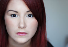 Sad redhead young woman with black eyes Royalty Free Stock Photo