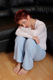 Sad Redheaded Woman. With blue pants and white shirt sitting on the hardwood floor. Her knees are bent, and her arms are crossed over her knees. Her face is stock photos