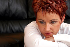 Sad Redheaded Woman. Closeup portrait of a redheaded woman with arms crossed in front of her.  Chin is resting on her hand.  Sad expression and evasive eyes Royalty Free Stock Images