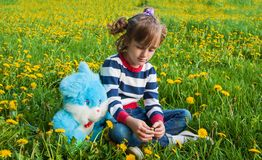 Sad, resentful child. Sad little girl with plush rabbit on the lawn Stock Photography