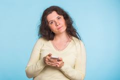 Sad and resentful woman waiting for excuses and explanations and is reproachfully looking  on blue background. Sad and resentful woman waiting for excuses and Royalty Free Stock Photos
