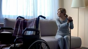 Sad retired lady waiting for husband at hospital, looking in window, rehab stock image