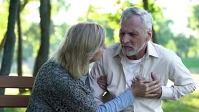 Sad retired man feeling heart pain, cardio problems, wife supporting husband