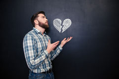 Sad romantic man holding drawn broken heart over blackboard background. Sad romantic young man holding drawn broken heart on palms standing over blackboard Stock Photo