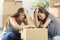 Sad roommates moving home after eviction. Sad roommates moving house together after eviction sitting on the floor at home Stock Photos