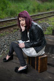 Sad runaway teen girl waits for train to escape her problem Royalty Free Stock Image