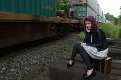Sad runaway teen girl waits for train to escape her problem. Teen girl with purple dyed hair sits beside railway tracks as train goes by Royalty Free Stock Photos