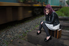 Sad runaway teen girl waits for train to escape her problem Stock Image